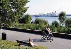 Elbwanderweg in HH-Nienstedten - Fahrradfahrer auf dem Weg an der Elbe - Parkbank in de Sonne - Frachtschiff auf der Elbe.