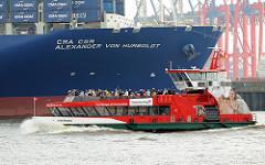 Bug vom Containerfrachter CMA CGM ALEXANDER VON HUMBOLDT im Hamburger Hafen - vollbesetzte Hafenfähre HARBURG passiert das Frachtschiff am Burchardkai.