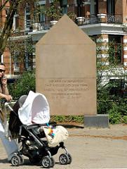 """Denkmal Wolfgang Borchert beim Schwanenwik; telefonierende Frau mit Kinderkarre - Inschrift """"Wir sind die Generation ohne Bindung und Tiefe. Unsere Tiefe ist der Abgrund. Wir sind eine Generation ohne Abschied, aber wir wissen, dass alle Ankunft uns"""