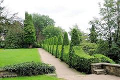 Weg mit kunstfertig geschnittenen Buchsbaumhecken im Römischen Garten von Hamburg Blankenese.