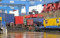 Beladung von Schuten mit Containern im Hamburger Hafen - eine der Stahlkisten wird auf einem der Lastkähne abgesetzt, die keinen eigenen Antrieb haben sonder von Schubschiffen bewegt werden.