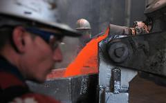 Arbeiter  lassen rot glühendes flüssiges Alluminium in die Form im Hamburger Aluminiumwerk in Altenwerder.