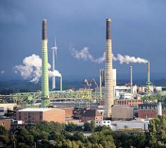 Weisser Qualm steigt aus den Schornsteinen; dunkler Gewitterhimmel über dem Hamburger Stadtteil Veddel.