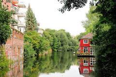 Ende des Isebekkanals - Wohnbebauung am Kanalufer in Hamburg Eimsbüttel - ein rotes Holzhaus spiegelt sich auf dem Wasser