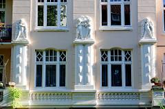 Stuckdekor an der Fassade eines Wohnhauses in Hamburg Eimsbüttel - Putten mit Blumenranken.