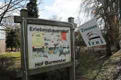 Schild an der Strasse Erlebnisbauernhof, Hof Burmester - Fahne Zimmer frei.