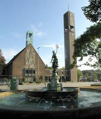 Puvogelbrunnen auf dem Marktplatz vom Hamburgrer Stadtteil Wandsbek - Kirchenschiff und Kirchturm der Wandsbeker Christuskirche.