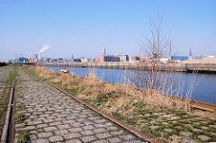 Petersenkai im Hamburger Baakenhafen - Gras und junge Bäume wachsen zwischen den Pflastersteinen und Schienen der Hafenbahn - auf der anderen Seite des Baakenhafens der Versmannkai. (2007)