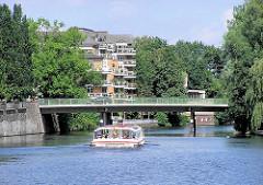 Ein Fahrgastschiff der Alsterflotte fährt auf dem Alsterkanal unter der Brücke Meenkwiese - im Hintergrund mehrgeschossige Neubauten am Ufer der Alster in Hamburg Eppendorf.