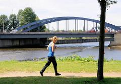 Eine Joggerin im Elbpark Entenwerder - im Hintergrund die Einfahrt zum Billhafen und dem Oberhafenkanal mit einer Strassenbrücke.