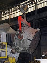 An einer Krananlage wird der Tiegel mit dem flüssigen Aluminium in der Werkshalle der Hamburger Aluminiumwerke transportiert.