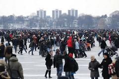 Blick au die zugefrorene Alster - die Hamburger und Hamburgerinnen gehen auf dem Eis spazieren.