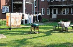 Innenhof in der Wohnanlage Friedrich Ebert Hof. Wäsche hängt zum Trocknen auf der Leine - ein Grill ist aufgestellt, der Tisch ist gedeckt.