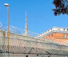 Gefängnismauer und Stacheldraht, Rückseite Hamburger Untersuchungsgefängnis am Holstenglacis, Spitze vom Hamburger Fernsehturm.
