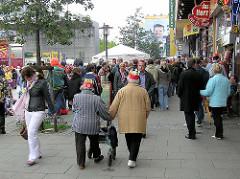 Passanten auf dem Spielbudenplatz / Reeperbahn Hamburg St. Pauli - re. Gewerbe / Läden, die zum Areal der Essohäuser gehören.