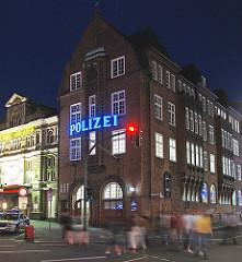 Hamburgs bekannteste Polizeiwache, die Davidwache in Hamburg St. Pauli. Fussgänger überqueren die Ampel.