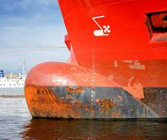 Rostiger Wulstbug eines Frachters im Hamburger Hafen - Markierung des Tiefgangs und Wulstbugzeichnung mit Seitenstrahlruder.