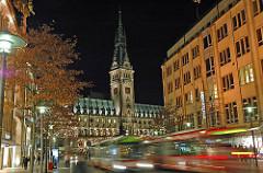 Hamburg am Abend - die Fassaden der Kontorhäuser und Geschäftshäuser in der Mönckebergstrasse sind beleuchtet. Das historische Hamburger Rathausgebäude ist hell angestrahlt. Zwei Autobusse fahren durch die Mönckebergstrasse.