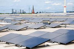 Solaranlagen auf dem 29 000 m² großen Dach des HHLA Logistikzentrums in Hamburg Altenwerder. Im Hintergrund der Kirchturm der St. Gertrudkirche des verlassenen Dorfes Altenwerder und rechts der Sockel der Windkraftanlage.