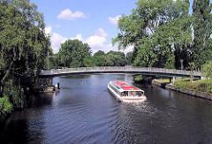Rundfahrt auf den Hamburger Kanälen - ein Ausflugsschiff fährt auf der Alster unter der Fussgängerbrücke, die den Kanal von Hamburg Eppendorf nach Winterhude überquert.