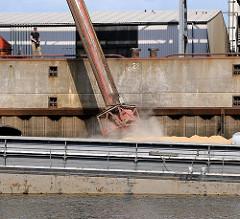 Beladen eines Binnenschiffs mit Schüttgut - über ein Rohr wird die Fracht in den Laderaum des Schiff eingeleitet.