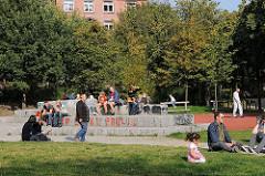 Menschen in der Sonne auf dem Kemal Altun Platz in Hamburg Ottensen.