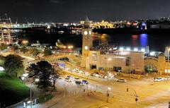 Nachtaufnahme der St. Pauli Landungsbrücken - auf der anderen Seite der Elbe das beleuchtete Zelt des Musicals König der Löwen.