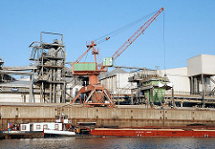 Eine Ladung Schüttgut wird mit einem Kran von einem Binnenschiff im Wilhelmsburger Reiherstieg gelöscht - Bilder aus den Hamburger Stadtteilen.