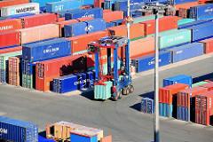 Ein Portalhubwagen transportiert einen Container auf dem Gelände des HHLA Container Terminals Burchardkai.
