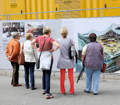 Vor der Baustelle der Hamburger Elbphilharmonie in der Hafencity sind grosse Informationstafeln angebracht, die anzeigen, wie das Konzerthaus wohl aussehen wird.