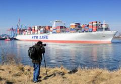 Ein Fotograf hält mit seiner Kamera auf einem Einbeinstativ / Monopod das Ablegen des Containerriesen NYK HELIOS im Hamburger Hafen fest.