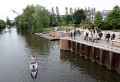 BesucherInnen des Jarreplatzes am Ufer des Osterbekkanals in Hamburg Winterhude / Jarrestadt - Kanu auf dem Kanal.