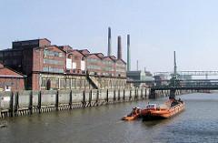 Eine Schute wird von einem Schlepper im Müggenburger Kanal gezogen - am Ufer historische Industrie-Ziegelgebäude auf der Peute in Hamburg Veddel.
