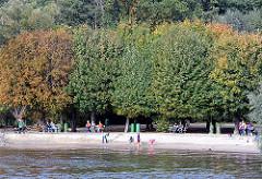 Herbstbäume am Elbufer bei Hamburg Wittenbergen - Kinder spielen am Wasser der Elbe.
