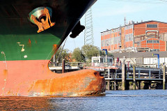 Wulstbug mit Delle und Anker des Frachtschiff RICKMERS TOKYO - an Land Industriearchitektur im Hamburger Stadtteil Wilhelmsburg.