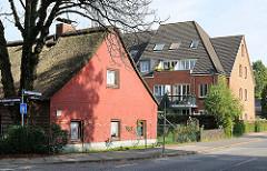 Historisches Reetdachgebäude und moderner Neubau im Hamburger Stadtteil Rissen.