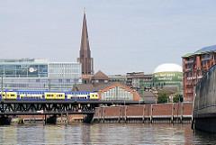 Ein Zug fährt über die Oberhafenbrücke - daneben das ehem. Marktgebäude in dem sich jetzt das Haus der Fotografie befindet. Im Hintergrund der Turm der Hamburger St. Jacobikirche.