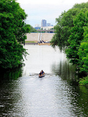 Ruderboot zwischen Bäumen im Ernst August Kanal von Hamburg Wilhelmsburg - im Hintergrund der Anleger der neuen Schleusenanlage.