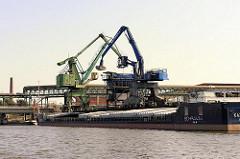 Kräne am Ufer des Müggenburger Kanals löschen die Ladung eines Binnenschiffs - Bilder von der Peute in Hamburg Veddel - Industriegebiet Hamburgs.