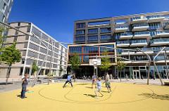 Spielfeld für Basketball in der Hamburger Hafencity - Vasco da Gama Platz - Jugendliche spielen vor moderner Architektur.