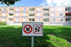 Hinweisschild mit Symbolen - Verbot von Fussball und scheissenden Hunden - zweistöckiger Wohnblock mit Balkons in der Sonne.  Bilder aus dem Hamburger Stadtteil Osdorf.