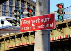 rotes Stadtteilschild Rotherbaum, Bezirk Eimsbüttel mit weisser Schrift am Dammtorbahnhof - Ampeln auf Rot.