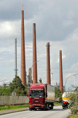 Schornsteine einer Erdölraffinerie in Hamburg Wilhelmsburg - Lastwagen auf der Strasse.