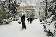 Fussweg durch den Hölderlinspark in der Jarrestadt in Hamburg Winterhude - ein Vater zieht sein Kind auf dem Schlitten durch den Schnee.