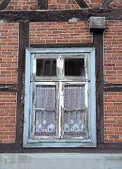 Historisches Harburger Fachwerkgebäude, restaurierungsbeduerftiges Holzfenster.
