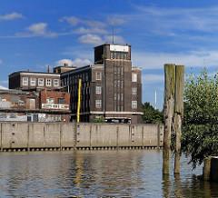 Billehafen in Hamburg Rothenburgsort - Alte Holzdalben im Wasser. Backsteinkontorhaus am Brandshofer Deich - Hamburger Architekturgeschichte.