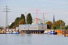 Blick über den Travehafen zur Polizeistation der Wasserschutzpolizei - zwei Polizeiboote liegen vor dem Gebäude - im Hintergrund die entstehende Elbphilharmonie mit den hohen Baukränen; rechts der Turm der St. Nikolaikirche.