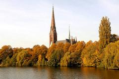 Herbstbäume am Ufer des Kuhmühlenteichs in Hamburg Uhlenhorst - herbstlich gefärbte Blätter - Kirchturm der St. Gertrudenkirche.