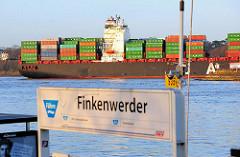 Schild Anlegestelle Fähre Hamburg Finkenwerder - ein beladenes Containerschiff fährt Richtung Hamburger Hafen.