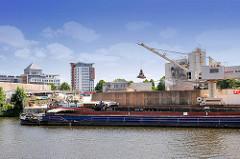 Löschen der Ladung Schüttgut eines Binnenschiffs mit einem Greiferkran im Billekanal von Hamburg Rothenburgsort.